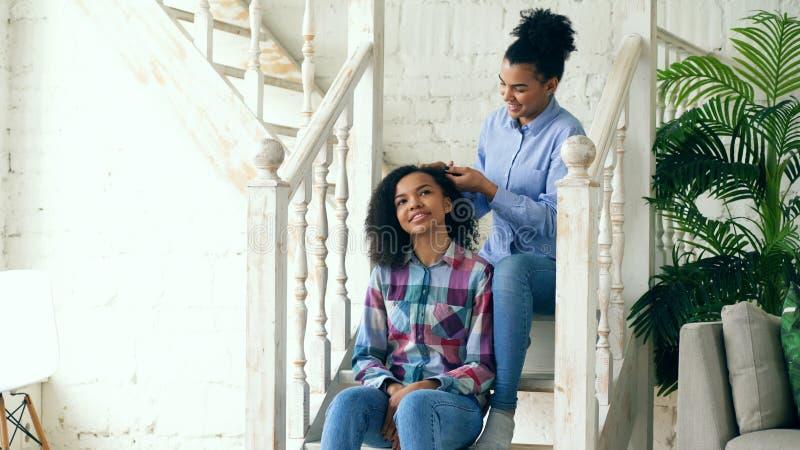 Dos sistres rizados afroamericanos de las muchachas hacen diversión el peinado rizado y se divierten en casa foto de archivo