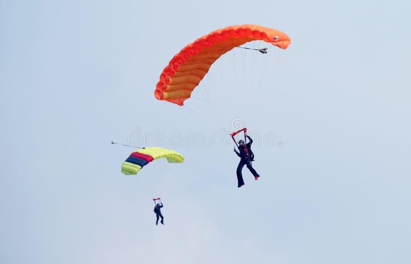 Dos skydivers con los canales inclinados coloridos que circundan en la cola para el landin fotografía de archivo