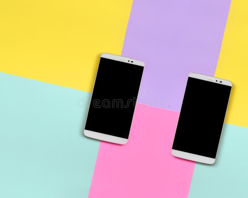 Dos smartphones modernos con las pantallas negras en el fondo de la textura de colores azules de la moda, amarillos, violetas y r imagen de archivo libre de regalías