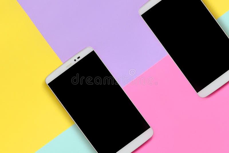 Dos smartphones modernos con las pantallas negras en el fondo de la textura de colores azules de la moda, amarillos, violetas y r fotos de archivo