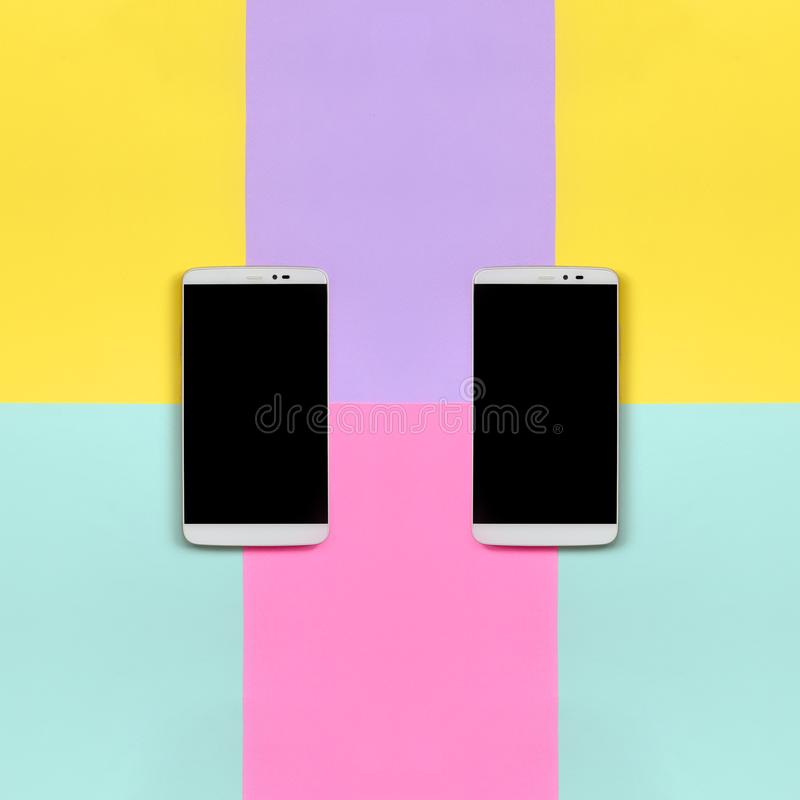 Dos smartphones modernos con las pantallas negras en el fondo de la textura de colores azules de la moda, amarillos, violetas y r fotos de archivo libres de regalías