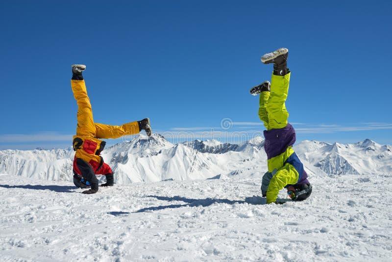 Dos snowboarders son a mano al revés en altas montañas fotografía de archivo libre de regalías
