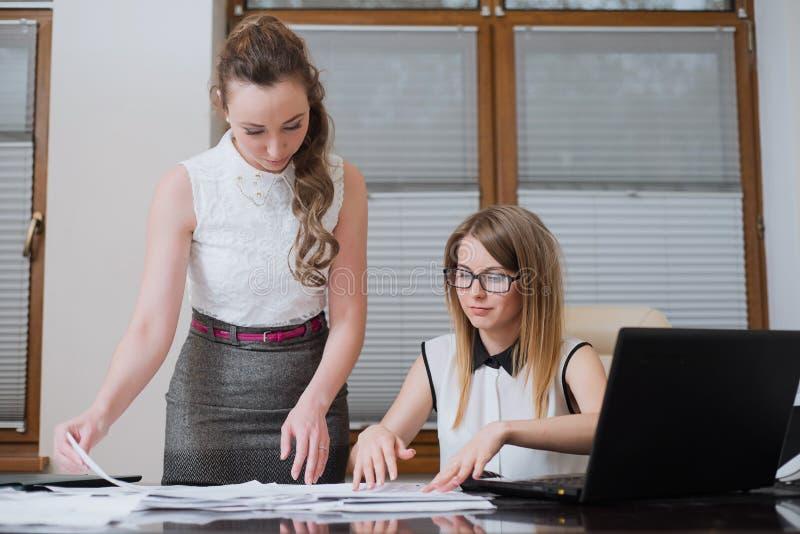Dos socios comerciales de las mujeres miran en estados financieros, estadísticas y documentos fotos de archivo libres de regalías
