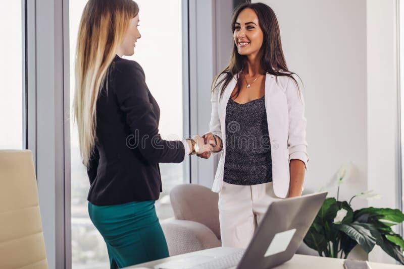 Dos socios comerciales elegantes que sacuden las manos después de la negociación acertada en sala de conferencias foto de archivo