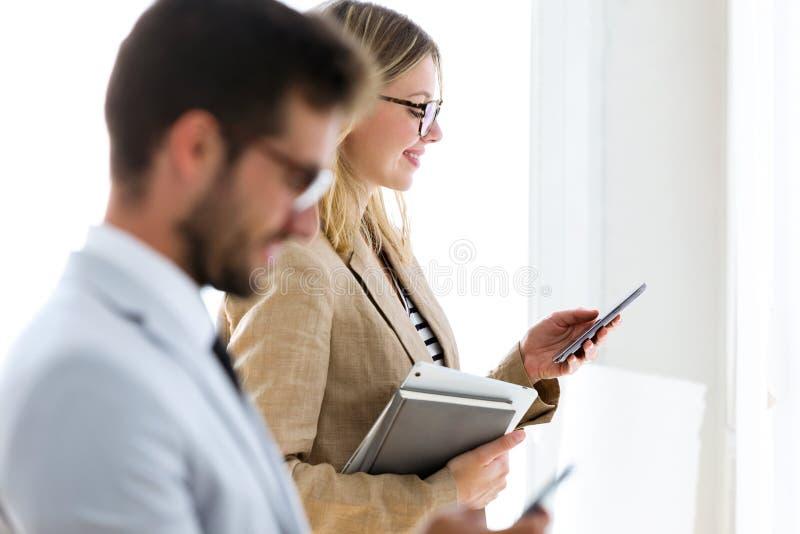Dos socios comerciales jovenes felices que mandan un SMS con sus smartphones en un vestíbulo de ellos compañía imágenes de archivo libres de regalías