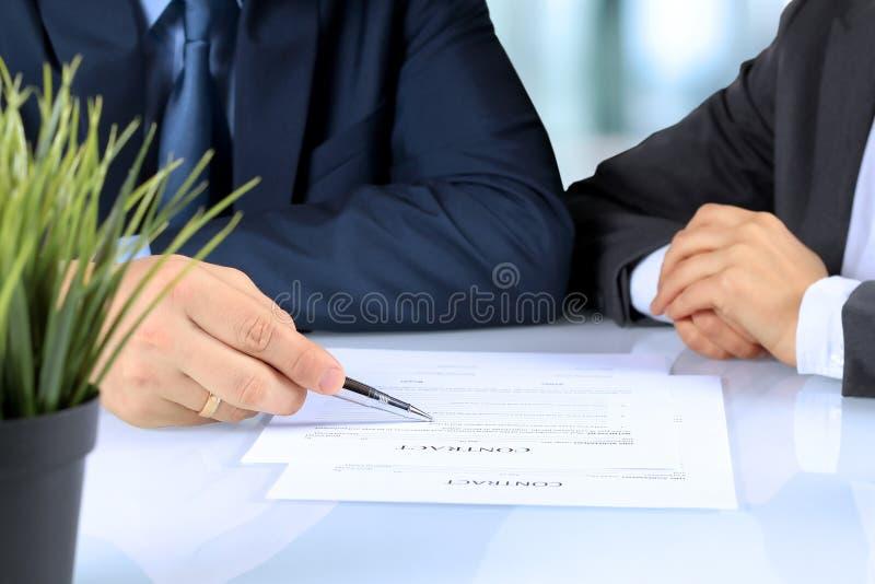 Dos socios comerciales que firman un documento foto de archivo