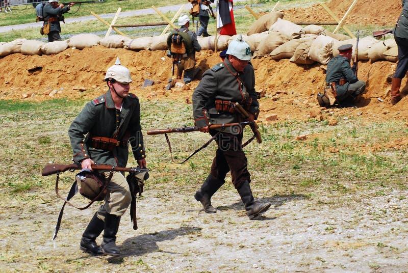 Dos soldados alemanes corren en el campo de batalla que sostiene los armas fotografía de archivo