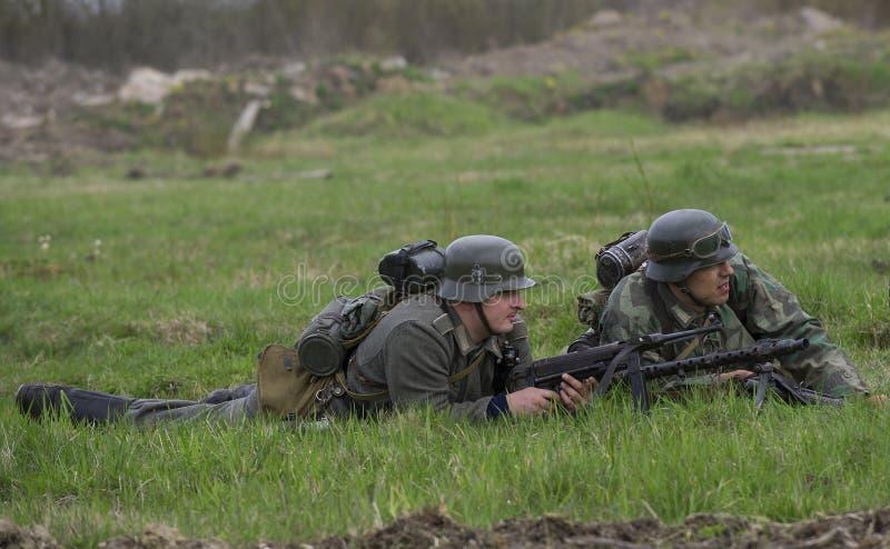 Dos soldados de Wehrmacht que mienten en la hierba Reconstrucción del episodio de la gran guerra patriótica imagen de archivo