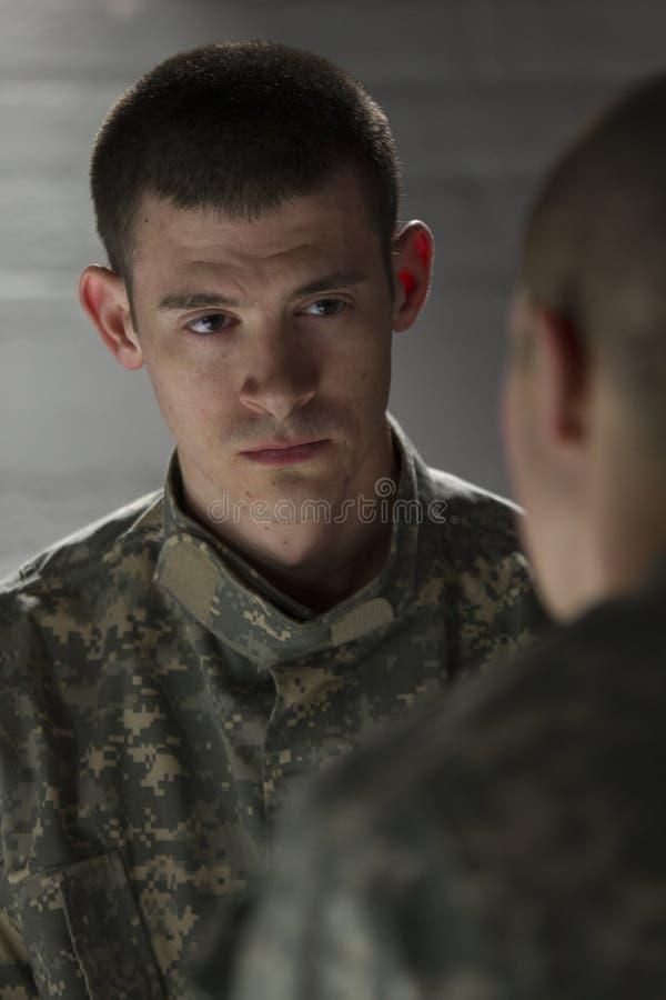 Dos soldados que se encuentran en el sitio oscuro, vertical imagenes de archivo