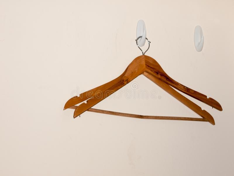 Dos suspensiones de ropa de madera en el fondo blanco de la pared vacian fotos de archivo