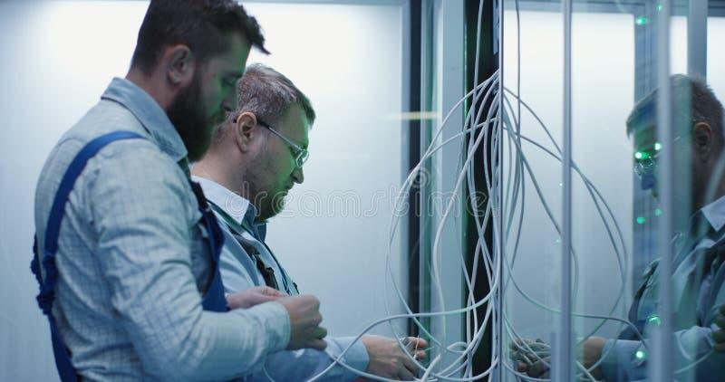 Dos técnicos de sexo masculino que trabajan en un centro de datos foto de archivo libre de regalías
