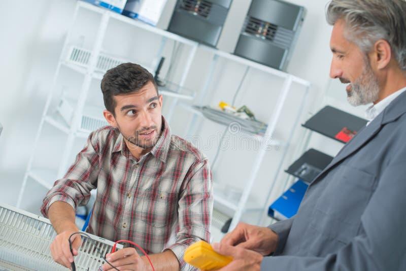 Dos técnicos que usan el multímetro en aparato eléctrico imagenes de archivo