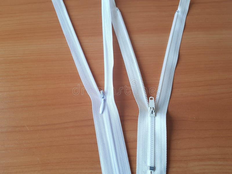 Dos tapones blancos sobre una superficie de madera clara Accesorios de costura imagen de archivo