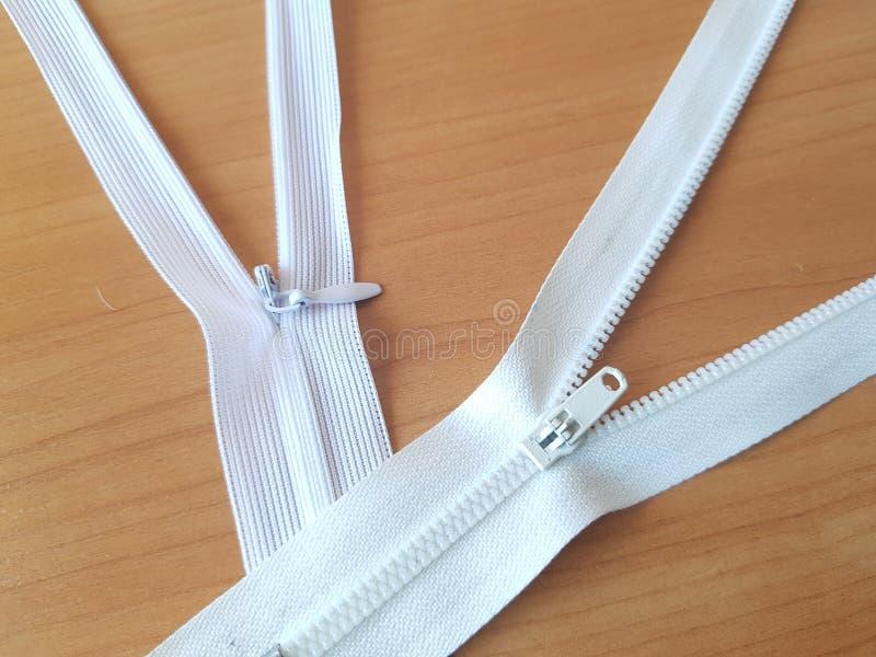 Dos tapones blancos sobre una superficie de madera clara Accesorios de costura imagenes de archivo