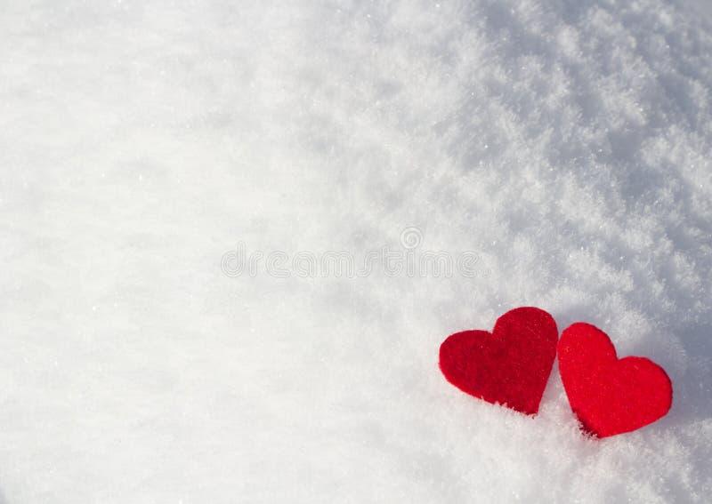 Dos tarjetas del día de San Valentín de mentira del color rojo en el invierno en la nieve fotografía de archivo libre de regalías