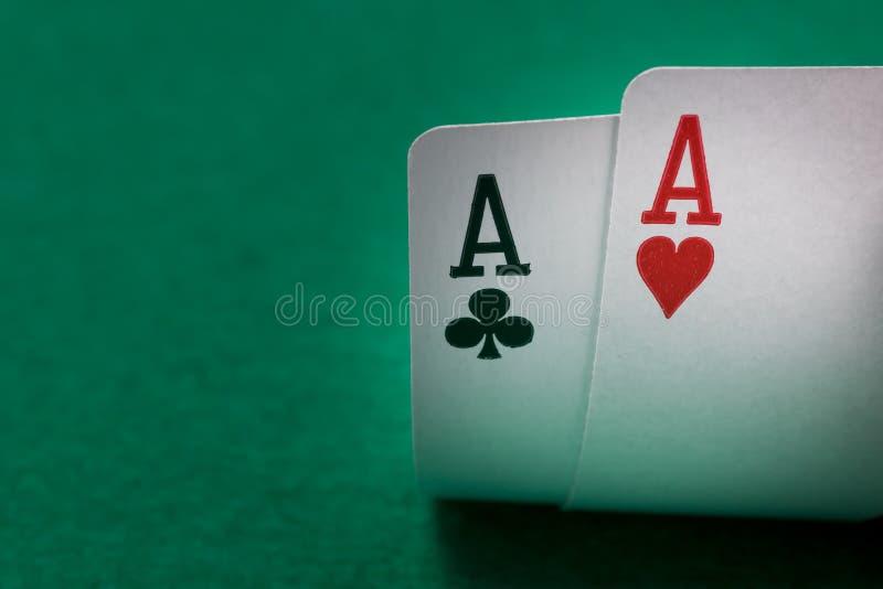 Dos tarjetas del póker de los as se cierran para arriba en una tabla verde imagenes de archivo