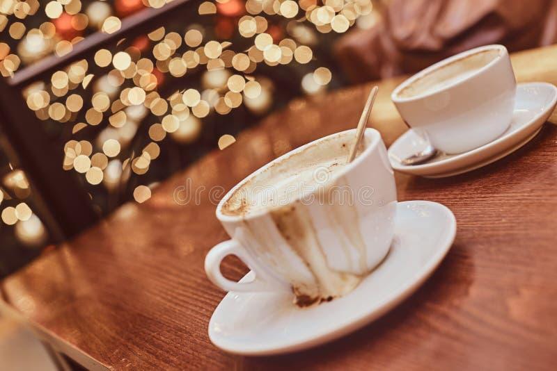 Dos tazas con café derramado en la tabla de madera en una cafetería, fondo de la falta de definición con efecto del bokeh imágenes de archivo libres de regalías