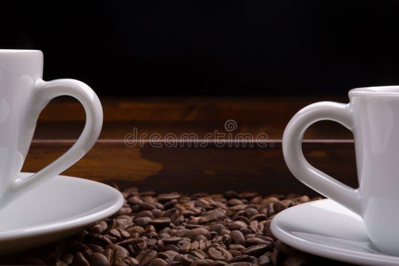 Dos tazas con las manijas en una bandeja por completo de granos de café fotos de archivo