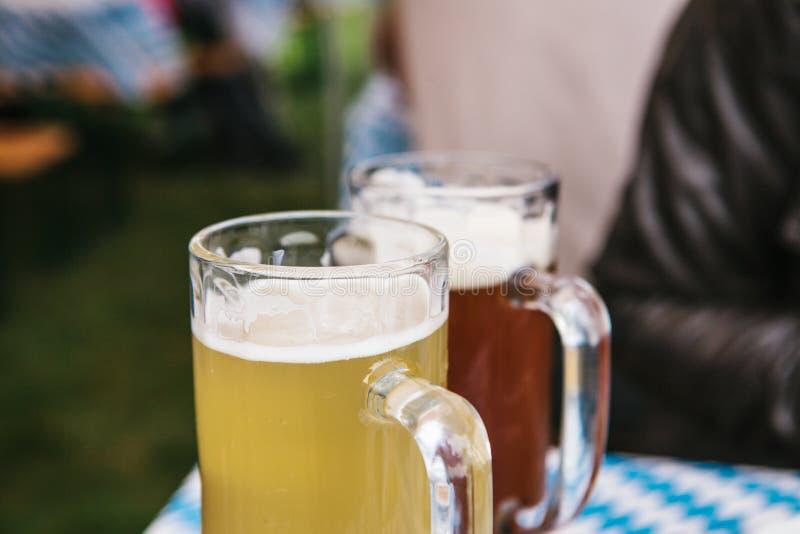 Dos tazas con un soporte de la cerveza ligera y oscura en la tabla Celebrando el festival alemán tradicional de la cerveza llamad fotografía de archivo libre de regalías