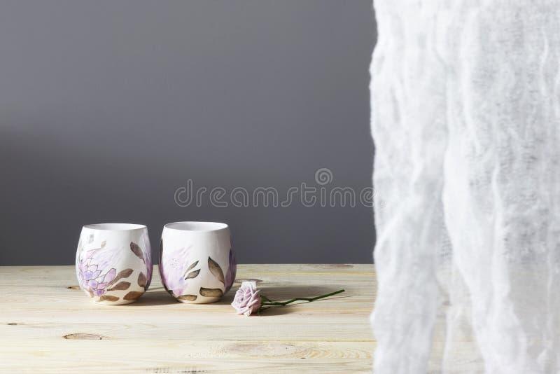 Dos tazas, cuenco con agua, toalla, flores de la primavera en el escritorio de madera mañana asoleada Desayuno foto de archivo libre de regalías