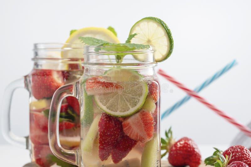 Dos tazas de agua de restauración de la fruta hecha de las fresas, del limón, de la menta y de la cal en el fondo, pajas de beber foto de archivo