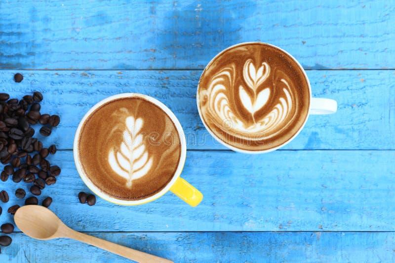 Dos tazas de arte del latte con el modelo las hojas y los granos de café en fondo de madera azul fotos de archivo