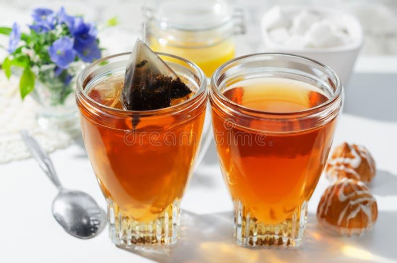 Dos tazas de bolsitas de té, de galletas y de miel calientes El proceso de preparar t? Foco selectivo imágenes de archivo libres de regalías