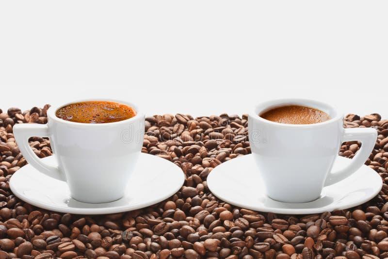 Dos tazas de café caliente con los granos de café en el fondo blanco foto de archivo libre de regalías
