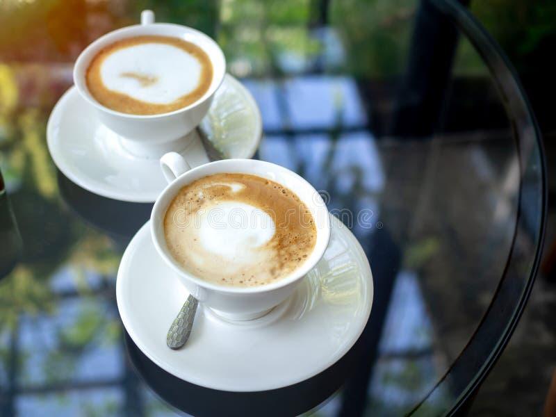 Dos tazas de café de cerámica blancas en la tabla de cristal imágenes de archivo libres de regalías