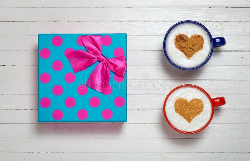Dos tazas de café con el corazón forman símbolo y la caja de regalo imagenes de archivo