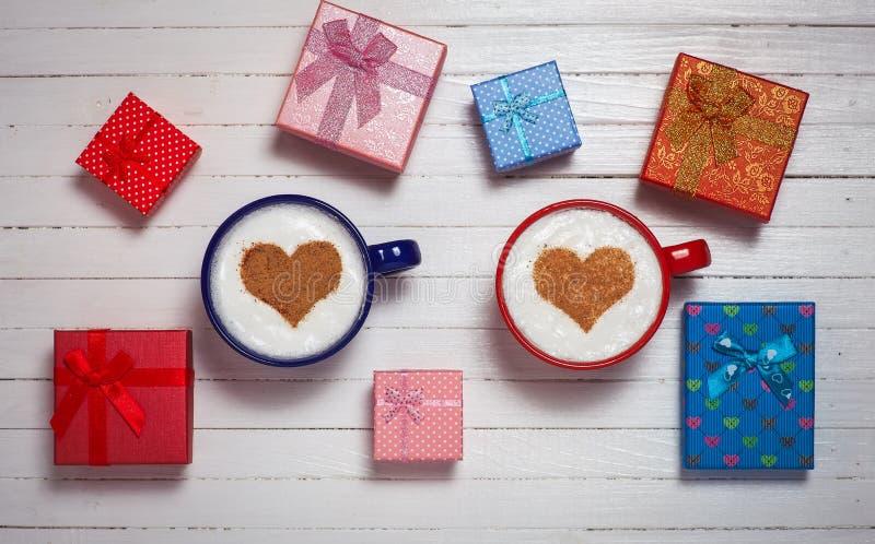 Dos tazas de café con el corazón forman símbolo y las cajas de regalo fotos de archivo