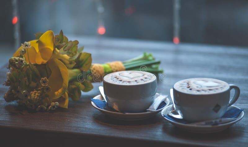 Dos tazas de café con un ramo de la boda fotografía de archivo