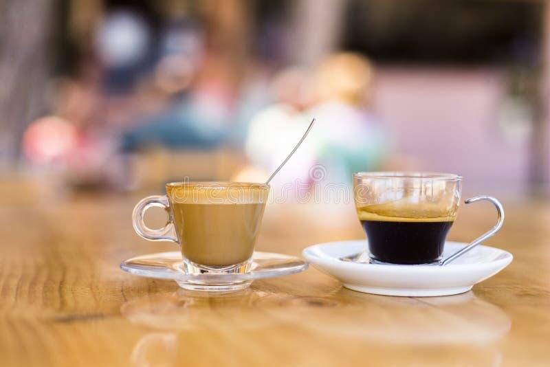 dos tazas de café en una tabla de madera en una terraza Verano, gente en el fondo Días de fiesta y forma de vida fotografía de archivo libre de regalías
