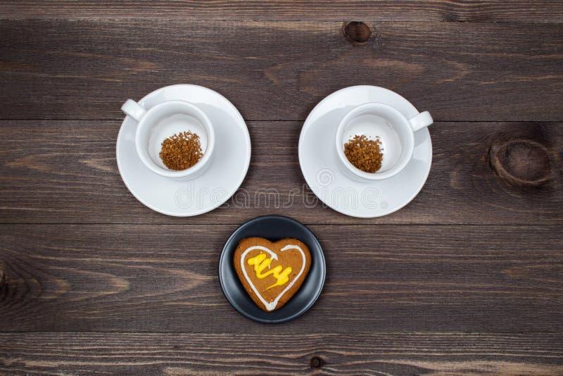 Dos tazas de café instantáneo y de galletas en forma de corazón en una tabla de madera imagenes de archivo