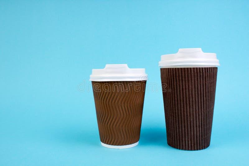 Dos tazas de café de papel disponibles, té aislado en el fondo blanco con el espacio de la copia imagen de archivo