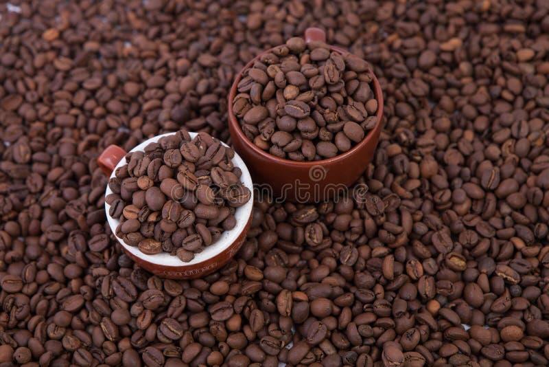 Dos tazas de café por completo de los granos de café Primer fotos de archivo