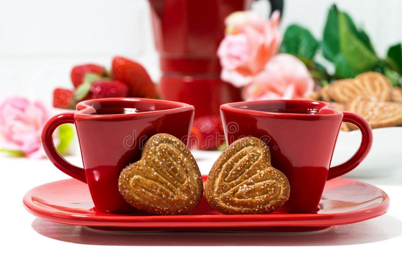 dos tazas de café rojas y galletas en forma de corazón en el fondo blanco imagen de archivo libre de regalías