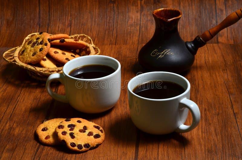 Dos tazas de café sólo con galletas americanas y un fabricante de café turco de la arcilla en fondo de madera del marrón oscuro fotos de archivo