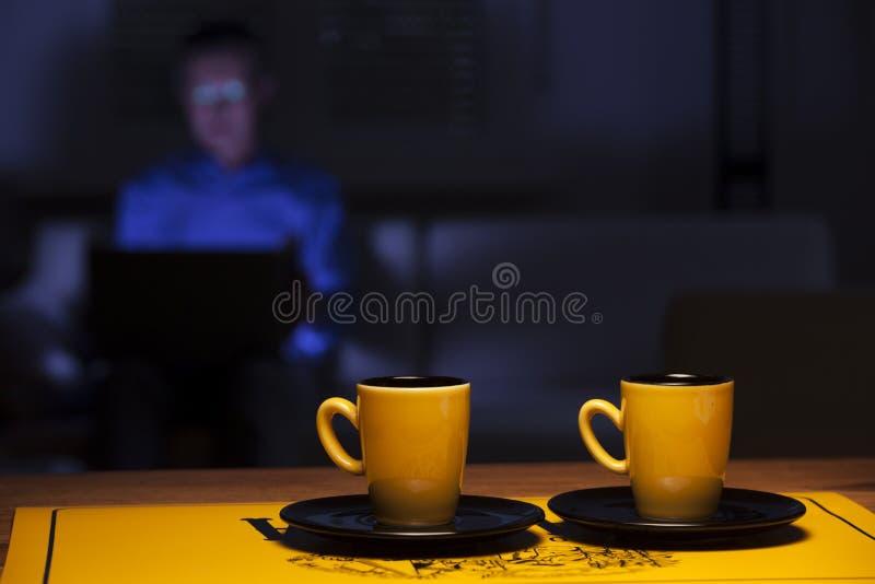 Dos tazas de café sobre una mesa y un hombre con un ordenador portátil fotos de archivo