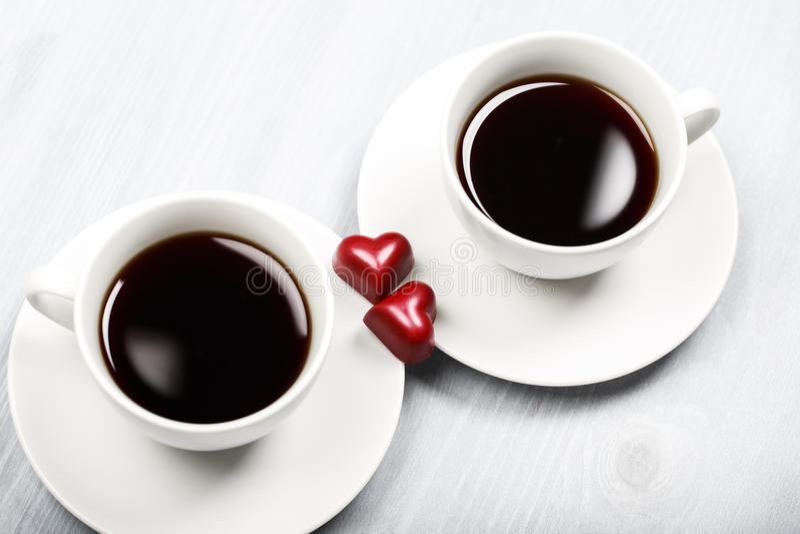 Dos tazas de café y de dulces en forma de corazón foto de archivo libre de regalías