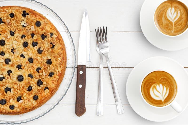 Dos tazas de café y de empanada hecha en casa con el soplo del requesón adornado con las almendras y los arándanos en la tabla de foto de archivo libre de regalías