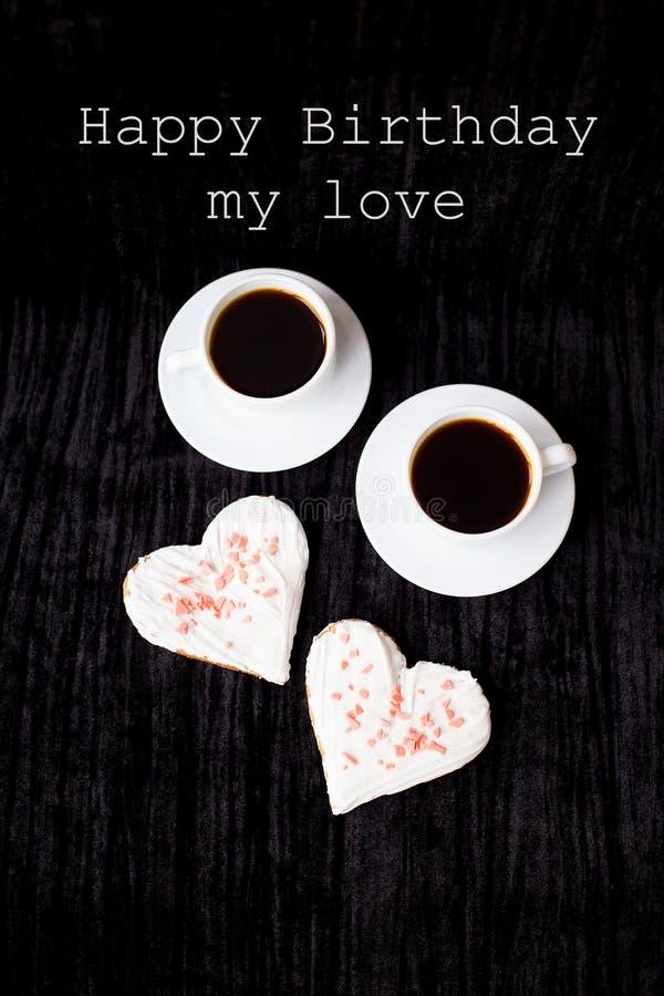 Dos tazas de café y de galletas bajo la forma de cumpleaños de la inscripción del corazón feliz mi amor foto de archivo