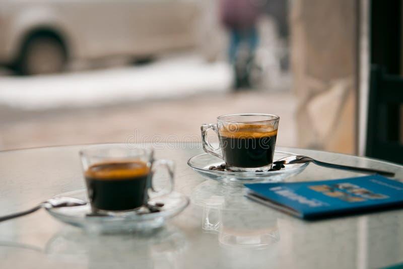 Dos tazas de cristal de café del americano en una tabla en un café en una mañana nublada de la primavera fotos de archivo