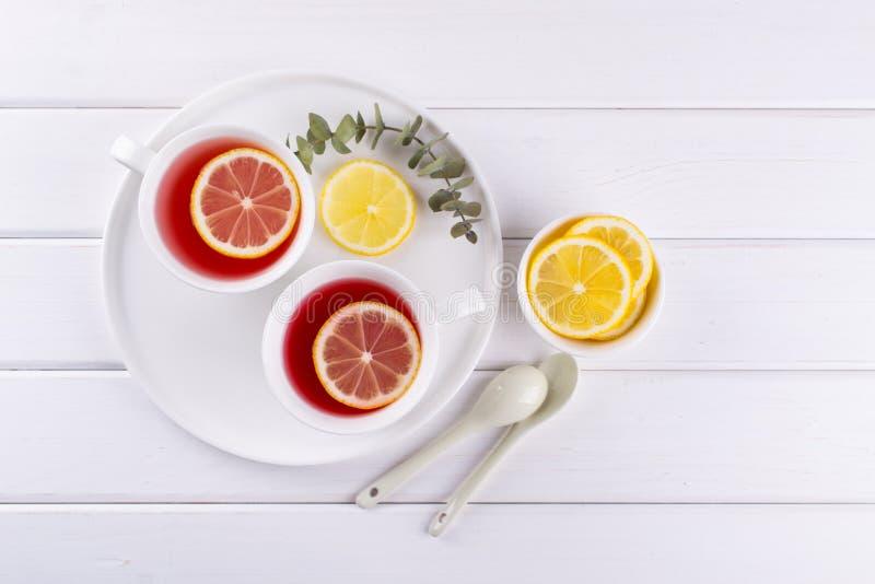 Dos tazas de fruta y de infusión de hierbas rojas con la rebanada del limón, imágenes de archivo libres de regalías