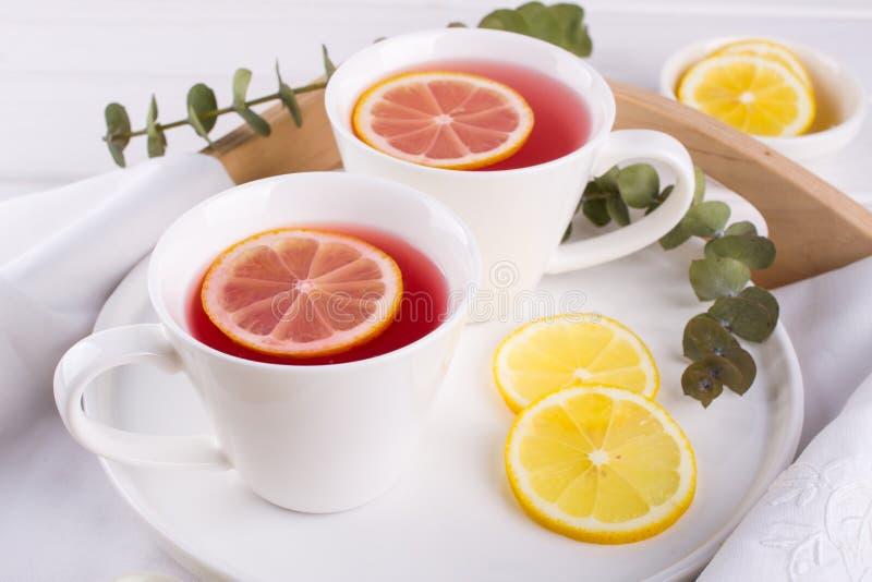 Dos tazas de fruta y de infusión de hierbas rojas con la rebanada del limón foto de archivo libre de regalías