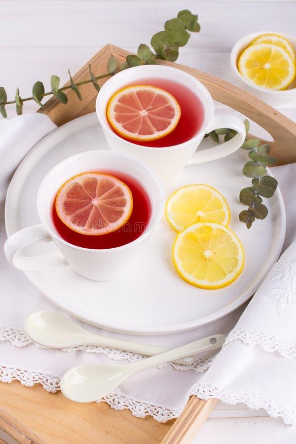Dos tazas de fruta y de infusión de hierbas rojas con la rebanada del limón fotos de archivo libres de regalías