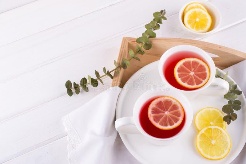 Dos tazas de fruta y de infusión de hierbas rojas con la rebanada del limón, fotografía de archivo