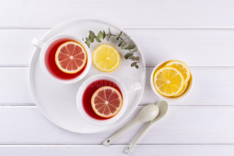 Dos tazas de fruta y de infusión de hierbas rojas con la rebanada del limón imagen de archivo libre de regalías