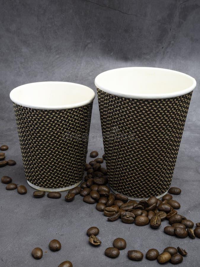 dos tazas de papel del caf? vac?o y granos de caf? fotos de archivo libres de regalías