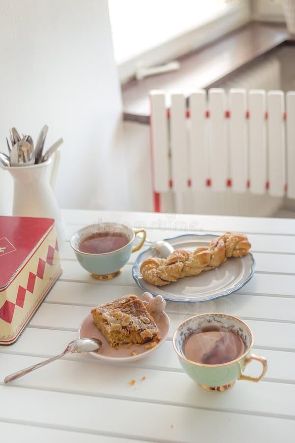 Dos tazas de té caliente con dos tortas en una tabla blanca foto de archivo
